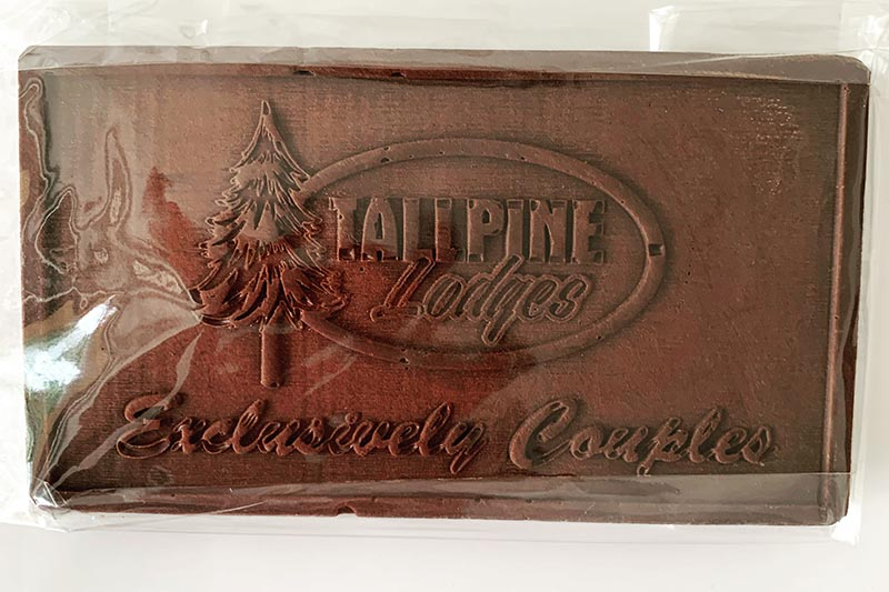 Chocolate bar with Tallpine Lodges logo. Text: Exclusively Couples.